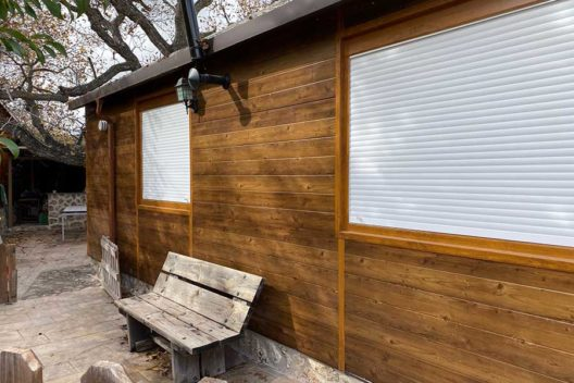 Casa de panel sándwich imitación madera con banco en exterior