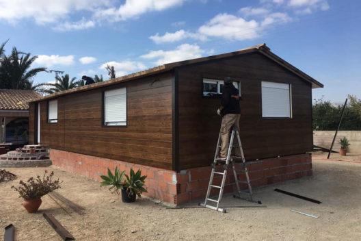 Casa de panel sándwich imitación madera con operario